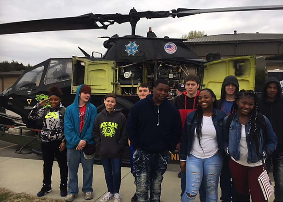 Hartsville High School students gather for a photo in front of a Cobra helicopter during a recent JROTC Aviation and STEM Day at the school.
